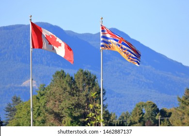 Two outdoor flags flying left to right on a flagstaff representing a Canadian and British Columbia emblem.