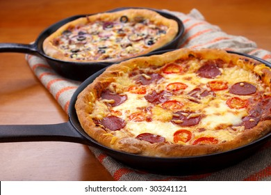Two oven cooked cast iron skillet pan pizzas on wooden table