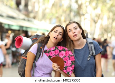 Two overwhelmed backpackers suffering heat stroke on summer vacation in the street