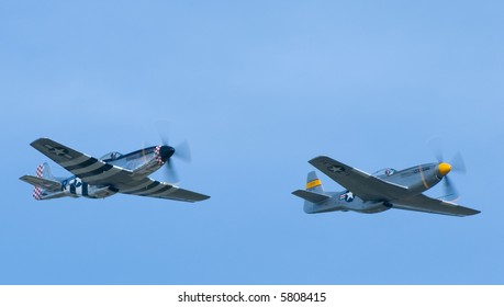 Two P-51 Mustangs flying in formation