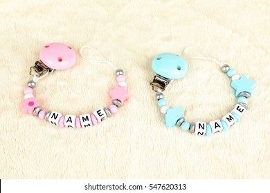 Two pacifier chains in blue and pink on a fur