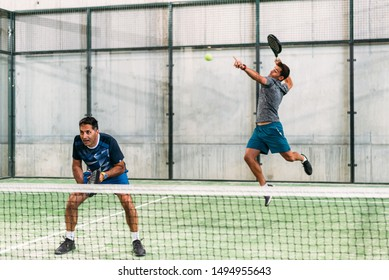two padel player playing padel in a green grass padel court indoor behind the net