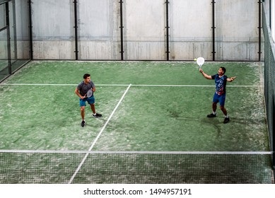 two padel player playing padel in a green grass padel court indoor