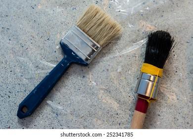 Two paint brushes laying on plastic underground