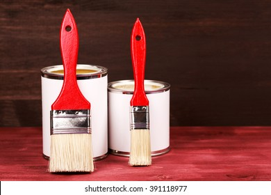Two paint cans with brushes