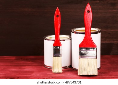 Two paint cans with brushes, lacquer or varnishing wooden floor.