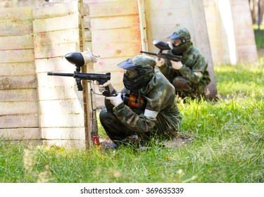 Two paintball players behind wooden fortifications