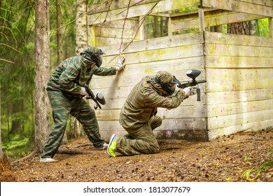 Two paintball players defending fortification