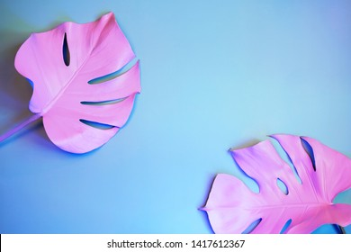 Two painted monstera leaves in neon light on blue background. Minimal art concept.