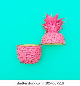 two painted in pink color halfs of the pineapple on turquoise background. fashion minimalism and surrealism of food. summer concept