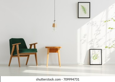 Two paintings of leaves on white wall and lamp above wooden table in relax room with dark green chair