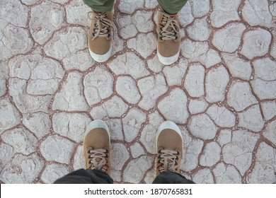 Two pair of feet on a dried crust in Dead Vlei, top view. Canvas hiking shoes standing on the ground, top view.