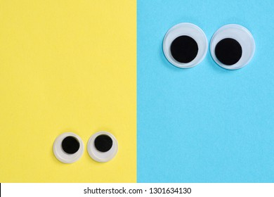 Two pair googly eyes on blue-yellow background look at each other, mad funny toys eyes close-up.