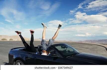 Two pair of legs upside down in a cabriolet car with copy space for the text / Death Valley / USA