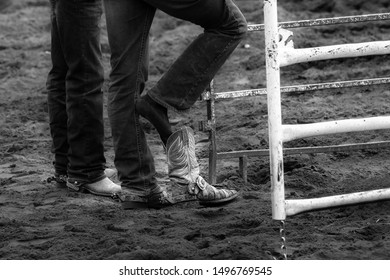 Two pair of male jean clad legs with one foot putting on a cowboy boot