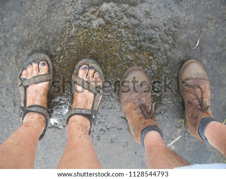 b71475ca3 Two pair of muddy feet (man wearing brown shoes and woman with sandals)  after a wet hike in rainy season looking down at their dirty feet - Image