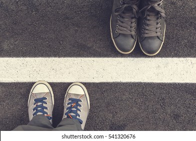 Two pair of sneakers on a asphalt road. Top of view.
