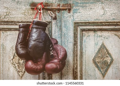 Two pair of vintage boxing gloves hanging on a weathered ancient wooden door with hinge