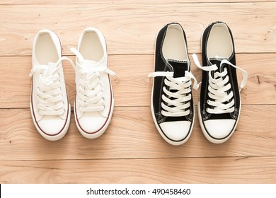 Two pairs of canvas shoes on a wooden