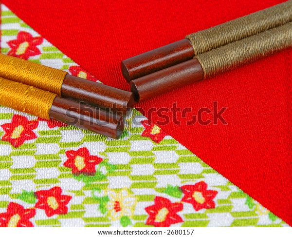 Two pairs of chopsticks on a specific piece of red Japanese fabric.