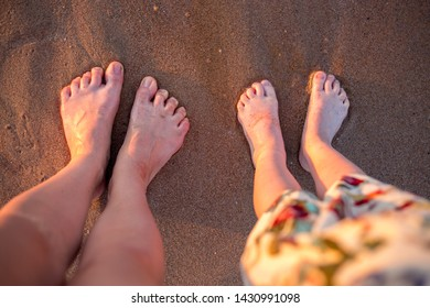 Two pairs of feet on the sand. Wet women's and children's feet on the beach. Body parts at sunset by the sea.