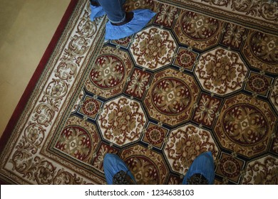 Two pairs of feet with plastic blue covers overshoes on an oriental carpet with brown hue patterns.