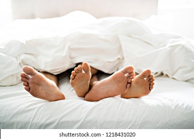 two pairs of feet under duvet couple makes love in bed