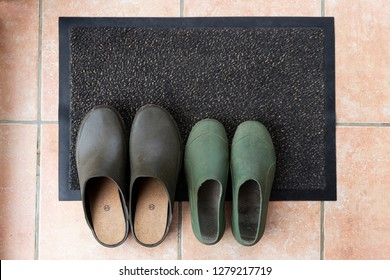 Two pairs of gardening shoes on an entrance rug: flat lay