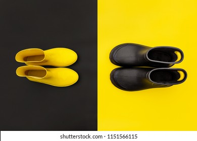 Two pairs of gumboots - yellow female and black male - standing opposite to each other on the inverse backgrounds. Top view. The concept of He and She