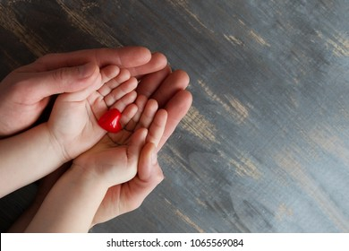 Two pairs of hands, men and children on a wooden background. They hold a tiny red heart in their hands. Top view, copy space.