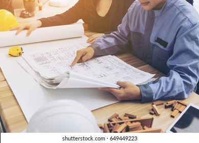Two pairs of hands sketching a housing project,teamwork concept.,Successful young architects discussing construction plans in construction site