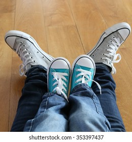 Two pairs of legs, child and mother or father with colorful sneakers and two pairs of jeans