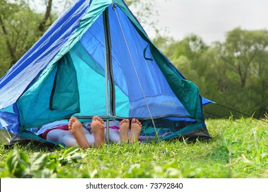 Two pairs of legs stick out from blue tent on a grassy glade meadow
