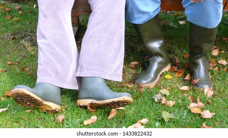 Two pairs of legs wearing green wellies at Wallington Hall and Gardens in Northumberland UK.