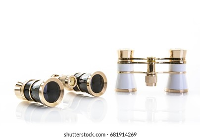 Two Pairs of opera glasses on a white background with refection and copy space