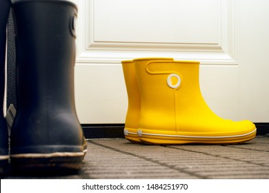 Two pairs of rubber boots standing in hallway near door. Close-up.