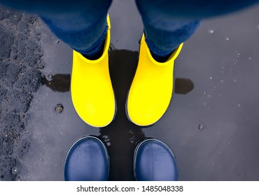 Two pairs of rubber boots standing in the puddle. Close-up.