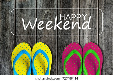 Two pairs sandals with text happy weekend on wooden background
