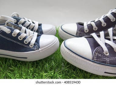Two pairs of sneakers, on the green grass. Sneakers of parent and child.