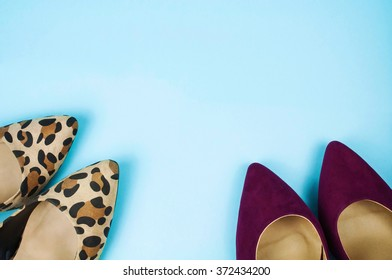 Two pairs of stiletto shoes in different colors and patterns on light blue background.