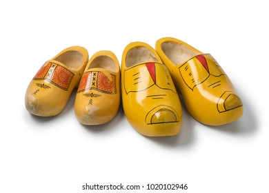 Two pairs of traditional yellow Dutch wooden shoes isolated on white background