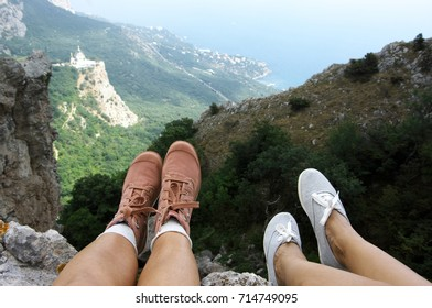 Two pairs of woman feet in textile boots over mountain landscape. Resting hikers on steep cliff.