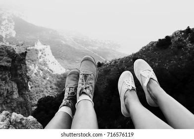 Two pairs of woman feet in textile boots over mountain landscape. Resting hikers on steep cliff. Black and white image.