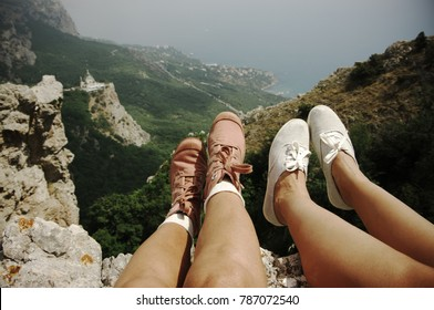 Two pairs of woman feet in textile boots over mountain landscape. Resting hikers on steep cliff. Vintage filtered image.