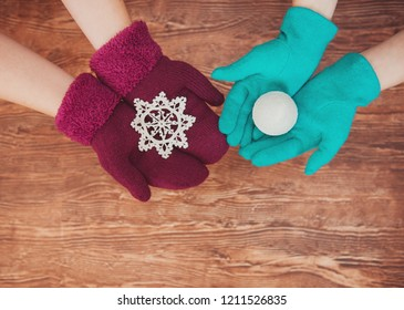 Two pairs of women hands knitted mittens holding a Christmas toy on a wooden background. Winter and Christmas concept.
