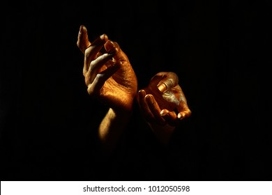 two palms of golden color on a black background