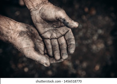 Two palms in mud and calluses are pointing up, hands of refugee and homeless. Concept hard work.