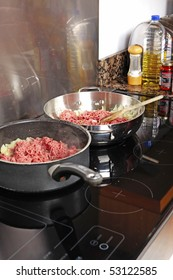 Two pans of ground beef cooking on a stove