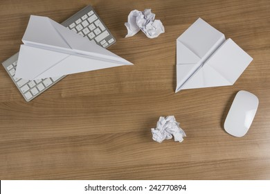 Two Paper Airplanes and balled up paper on a wooden office desk with modern keyboard and mouse