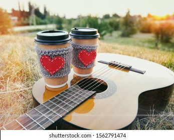 Two paper coffee cup in knitted cozy sleeves standing on guitar. Outdoor picnic sunset scene.